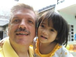 "Jim Altman poses for a photo with a Vietnamese orphan. This shot, he says, ""became our family vision for international adoption"""